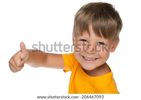 Young happy boy holds his thumb up on the white background - stock photo