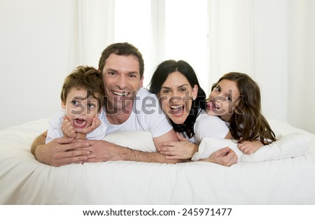 young happy Brazilian family playing together on bed with mother, father, daughter and son having fun smiling and laughing in bedroom in love and lifestyle concept - stock photo