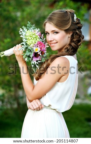 Young Happy Bride With Flower Bouquet in the summer park - stock photo