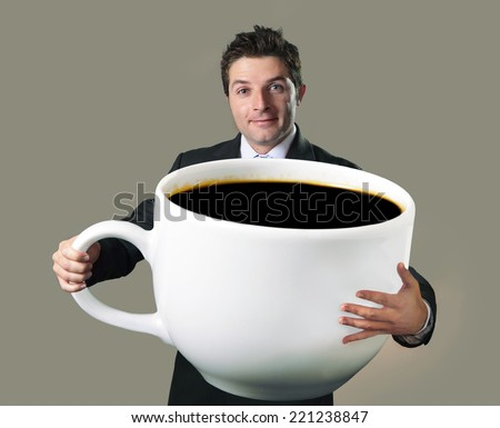 young happy business man holding a funny huge and oversized cup of black coffee in caffeine addiction concept isolated on even background - stock photo