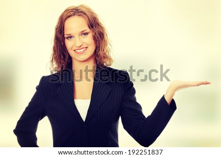 Young happy business woman showing copy space - stock photo