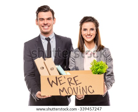 Young happy businessman and a business woman with boxes for moving into a new office. Studio shot, isolated on a white background - stock photo