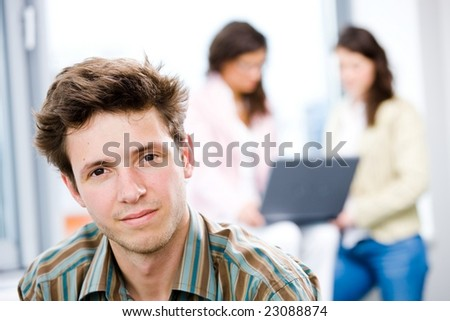 Young happy businessman looking at camera, smiling while business team working in background. - stock photo