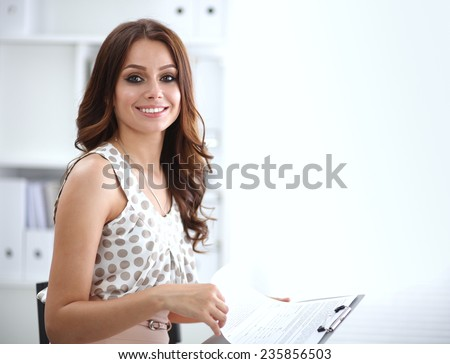 Young happy businesswoman in office holding  folder - stock photo
