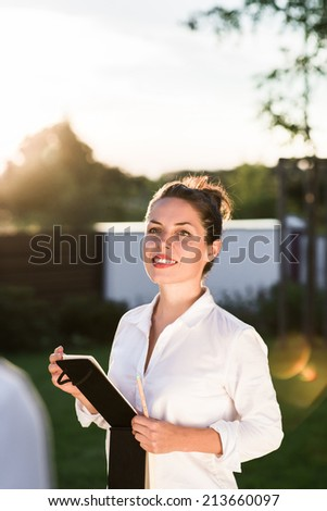 Young happy businesswoman or landscape architect speaking with her client. Young professional is dressed in casual clothes. Strong sunset backlit. - stock photo