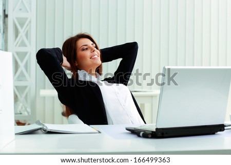Young happy businesswoman resting in office - stock photo