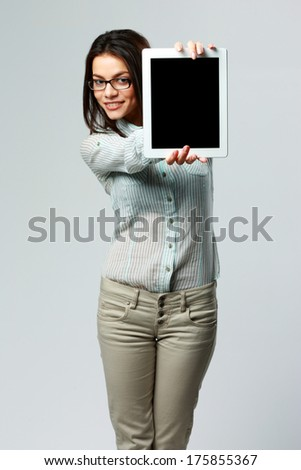 Young happy businesswoman showing tablet computer screen on gray background - stock photo