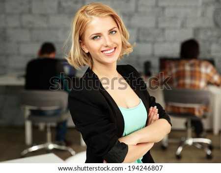 Young happy businesswoman standing on office - stock photo