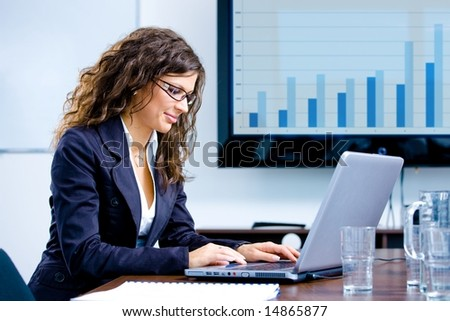 Young happy businesswoman working on laptop computer in meeting room at office, smiling. - stock photo