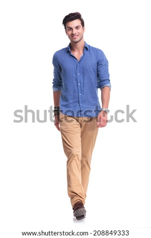 young happy casual man walking towards the camera on white studio background - stock photo
