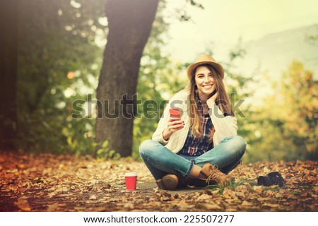 Young happy Caucasian blonde woman with smartphone, camera and coffee in park sitting among yellow leaves wearing casual clothes and hat smiling. - stock photo