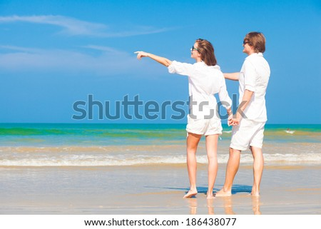 Young happy caucasian couple in white standing on beach looking at the sea - stock photo