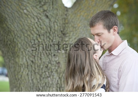 Young happy caucasian couple kissing in the park on a sunny day. - stock photo