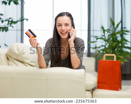 young happy caucasian woman holding credit card and shopping over the phone - stock photo