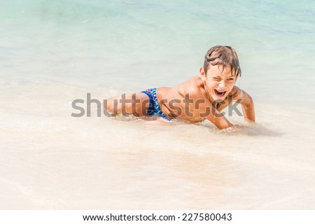 young happy child boy having fun in water, tropical summer vacations, holidays - stock photo