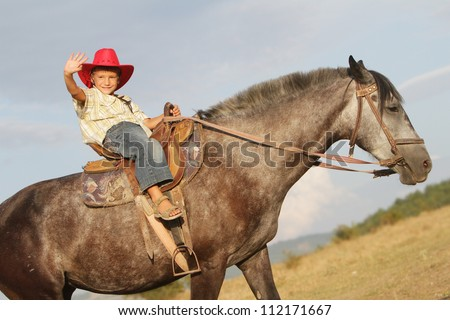 young happy child boy riding horse on natural background - stock photo