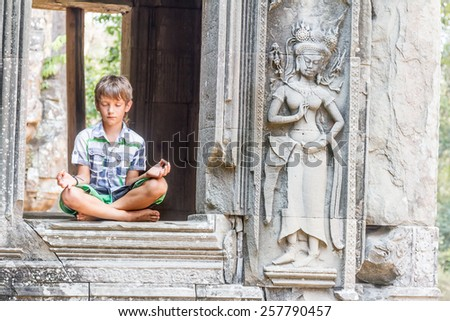 young happy child boy tourist meditating in angkor wat, cambodia - stock photo