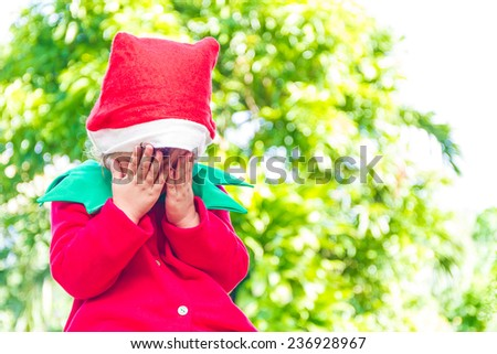 young happy child dressed as santa helper elf, xmas costume, green outdoor background - stock photo