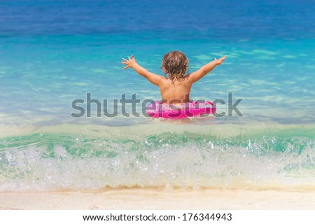 young happy child enjoying swimming on tropical beach - stock photo