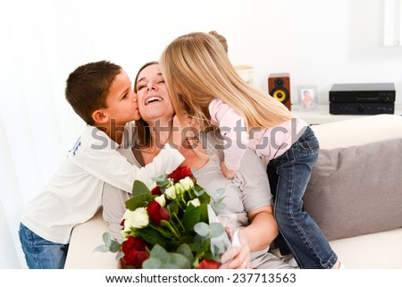 young happy children offering flowers to their mum during mother's day - stock photo