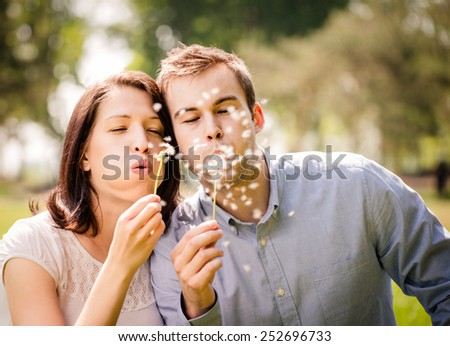Young happy couple blowing together dandelions, outdoor in nature - stock photo