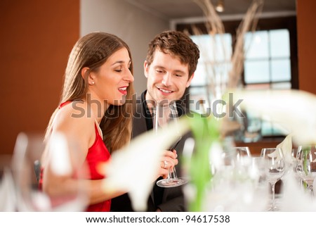 Young happy couple celebrating with red wine at restaurant - stock photo