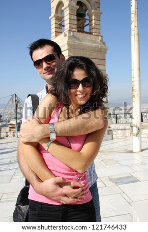 Young happy couple do sightseeing in Greek capital - city of Athens in a bright sunny day - stock photo