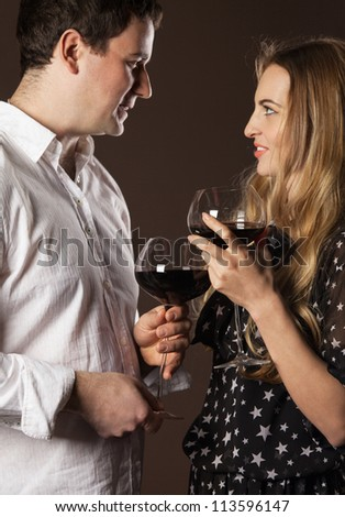Young happy couple enjoying a glasses of red wine - stock photo