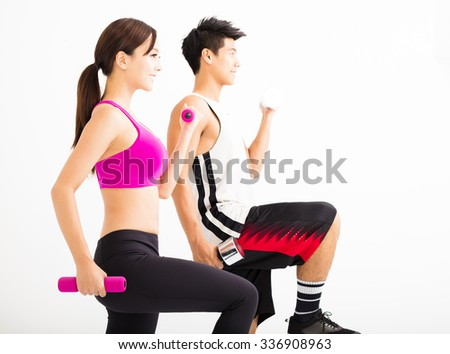 Young happy couple exercising with dumbbell - stock photo