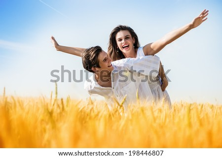 Young, happy couple have a piggy back in the wheat field.Summer season - stock photo