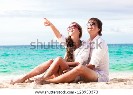 young happy couple having fun on tropical beach. honeymoon - stock photo