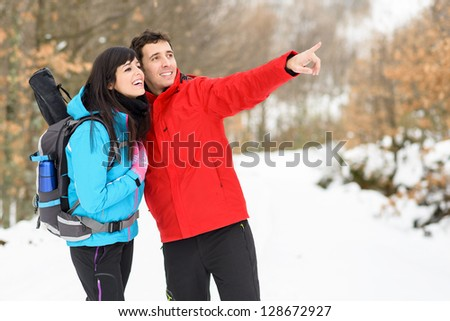 Young happy couple hiking on winter mountain forest. Smiling couple pointing and smiling during walking hike on nature vacations outdoors. Caucasian friends. - stock photo
