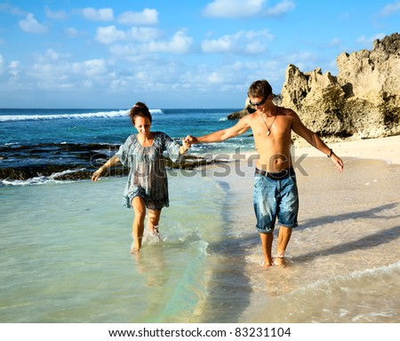 Young happy couple holding hands during a walk along the coast - stock photo