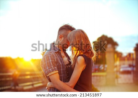 Young happy couple hugging on the sunset - stock photo