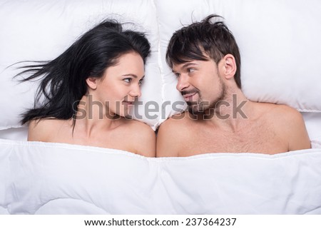 Young happy couple in a bed. Top view. They are looking at each other. - stock photo