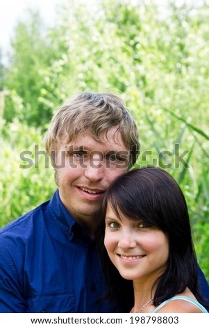young happy couple in front of green background - stock photo