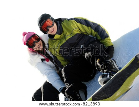 Young happy couple in goggles on snowboards - stock photo