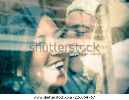 Young happy couple in love at the beginning of a Love Story - Fashion man whispers a soft kiss in the ear of the loved young woman - stock photo