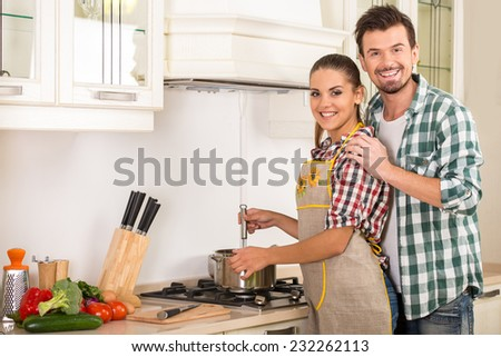 Young happy couple in the kitchen while cooking dinner. - stock photo