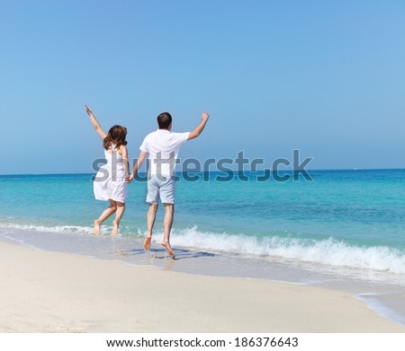 Young happy couple jumping on the beach holding hands - stock photo