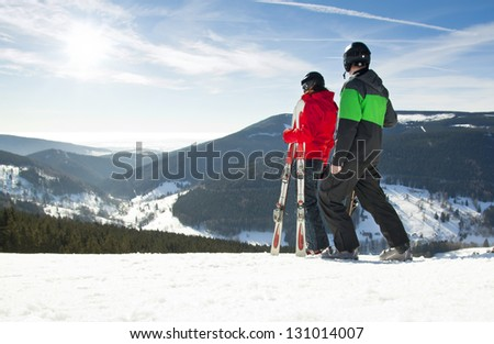 Young happy couple looking in snowy mountains holding ski, Czech - stock photo