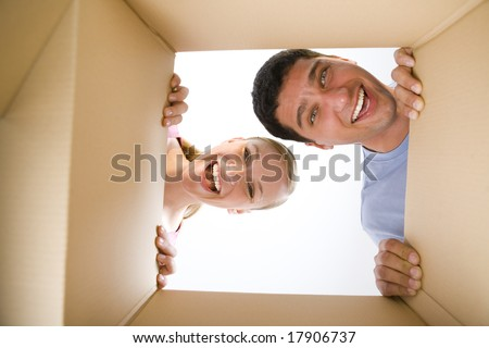 Young happy couple looking into cardboard box. They're looking at camera. Low angle view. - stock photo