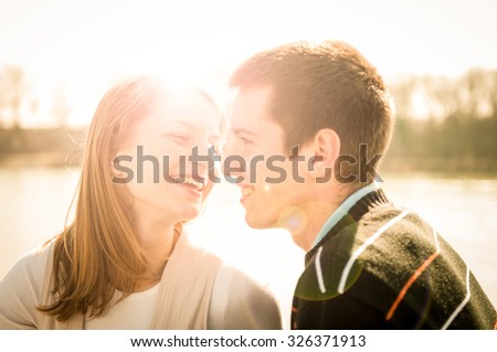Young happy couple looking on each other  - outdoor lifestyle portrait - stock photo