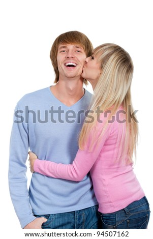 Young happy couple love smiling hug kiss, woman kissing excited man he looking at camera toothy laughing, isolated over white background - stock photo