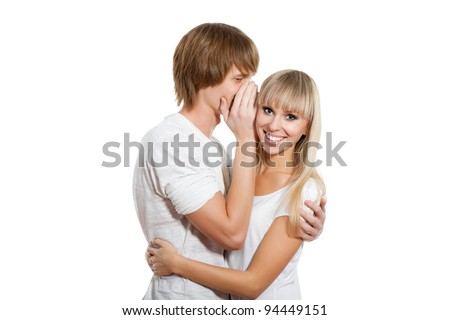 Young happy couple love smiling, man telling a secret to a girl - she is looking at camera laughing, isolated over white background - stock photo
