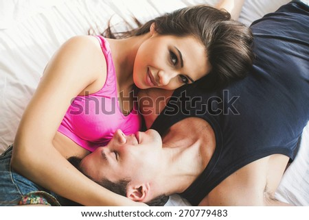 Young happy couple lying in bed in the sunny morning, smiling and having fun together - stock photo