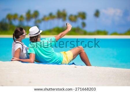 Young happy couple making a selfie with mobile phone on beach - stock photo