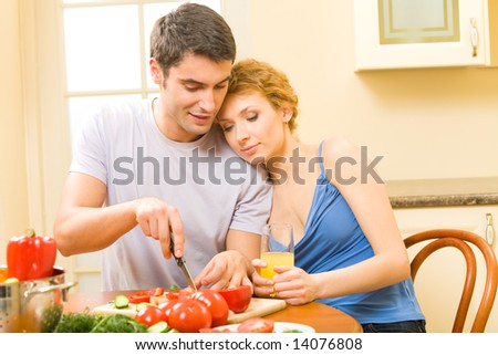 Young happy couple making salad at home together - stock photo