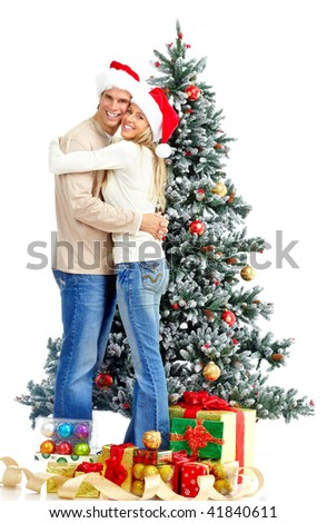 Young happy couple near  a Christmas tree. Over white background - stock photo