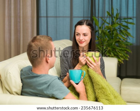 young happy couple on couch drinking coffee at home and laughing - stock photo